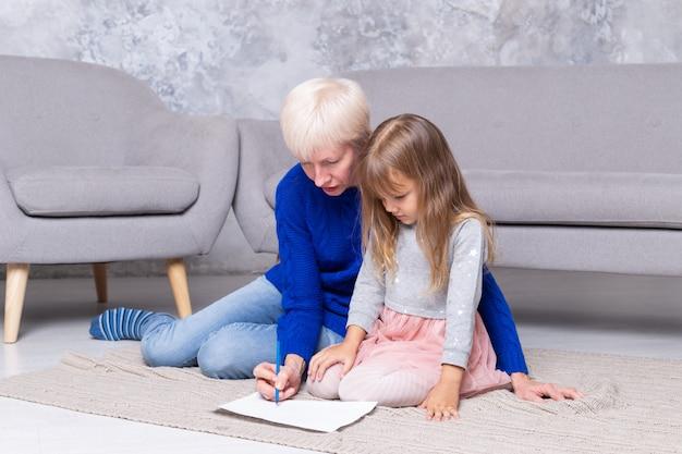 Avó e neta juntos pintam no chão da sala. mulher adulta ajuda a criança a desenhar uma imagem Foto Premium