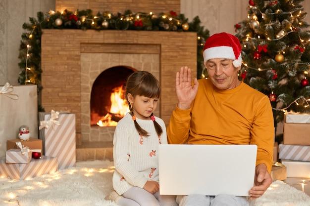 Avô e neta tendo um vídeo no notebook, acenando com as mãos para a câmera, parabenizando alguém com vésperas de ano novo, vestindo casualmente, sentado perto da lareira e a árvore de natal. Foto Premium