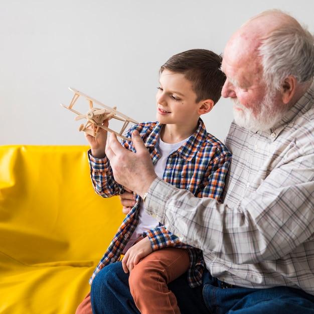 Avô e neto jogando avião de brinquedo Foto gratuita