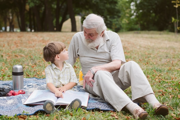 Avô e neto na leitura de piquenique Foto gratuita