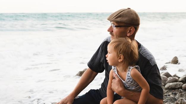 Avó e neto, olhando para o mar Foto gratuita