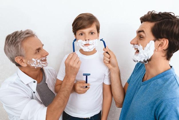 Avô e pai e filho com espuma de barbear nas faces. Foto Premium