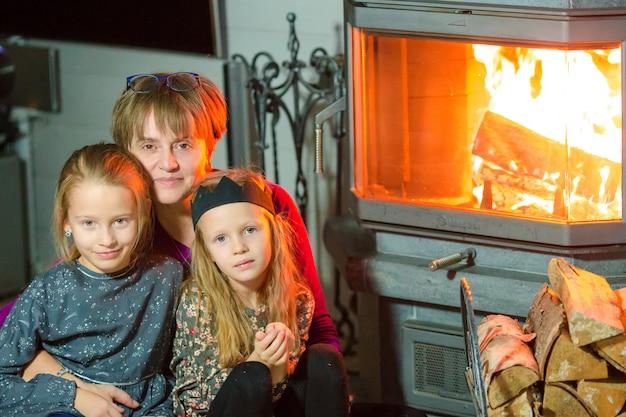 Avó e suas duas netas sentadas perto de uma lareira em sua casa de família na véspera de natal Foto Premium