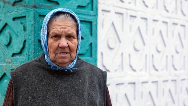 Avó em um lenço no fundo da parede de sua casa, o conceito de velhice. Foto Premium