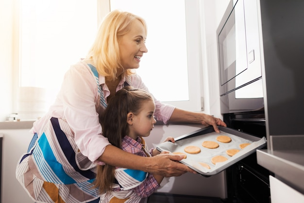 Avó ensina a garota a fazer biscoitos caseiros. Foto Premium