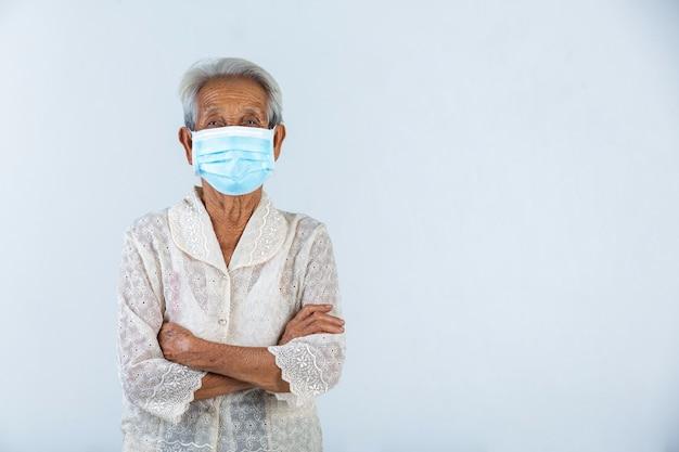 Avó está se abraçando e aproveite com sua vida na parede branca. - campanha de máscara de conceito. Foto gratuita