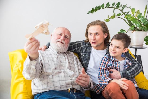 Avô feliz brincando com avião de madeira Foto gratuita