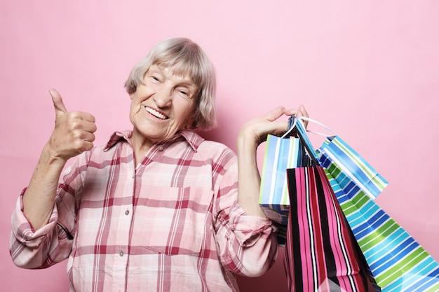 Avó feliz com sacos de compras sobre fundo rosa. estilo de vida e conceito de pessoas. Foto Premium