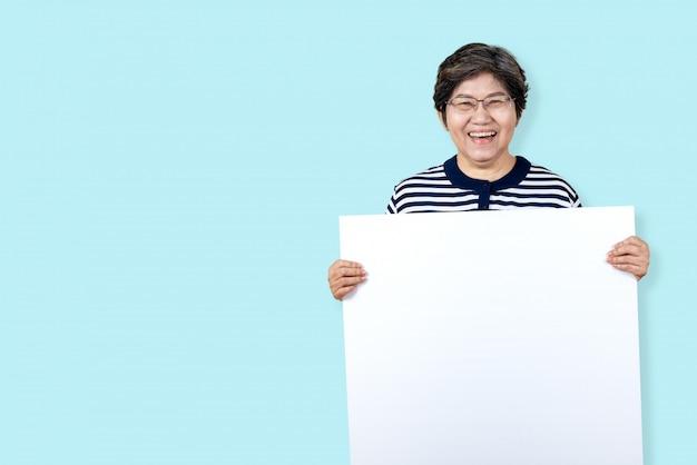 Avó feliz sorrindo com dentes brancos, aproveite o momento e segurando uma placa em branco. Foto Premium