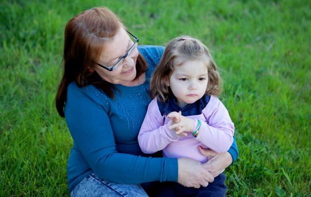 Avó orgulhosa com a neta sentada na grama Foto Premium