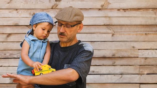 Avô, segurando neto com carro de brinquedo Foto gratuita