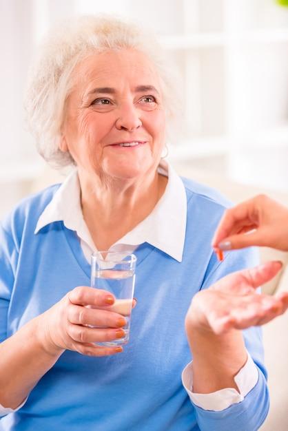 Avó senta-se e sorrisos mantém um copo de água. Foto Premium