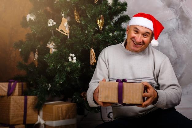 Avô senta-se perto de uma árvore de natal em uma cadeira com um grande presente Foto Premium