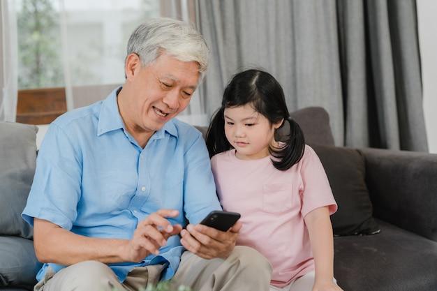 Avós e neta asiáticos usando o telefone celular em casa. o chinês sênior, vovô e criança felizes passam o tempo em família relaxar com a jovem garota verificando mídias sociais, deitado no sofá na sala de estar. Foto gratuita