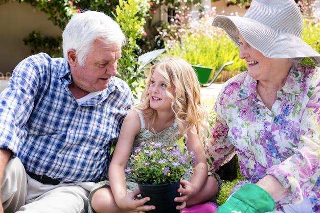 Avós e neta sentada no jardim Foto Premium