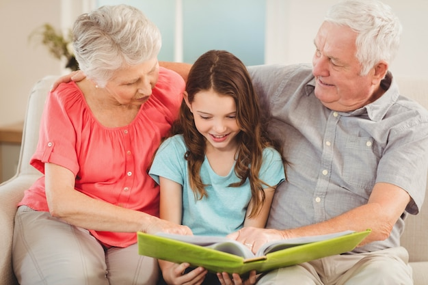 Avós e neta sentada no sofá e ler um livro com a neta Foto Premium