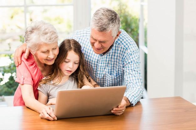 Avós e neta usando laptop em casa Foto Premium
