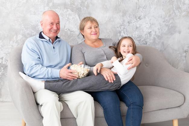 Avós, juntamente com neta assistindo tv, filme dentro de casa Foto Premium