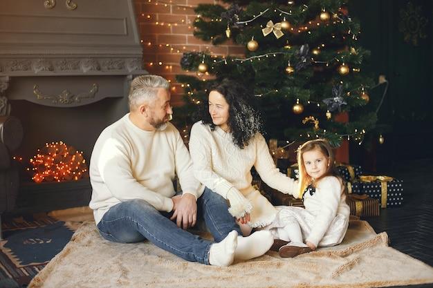 Avós sentados com a neta. comemorando o natal em uma casa aconchegante. Foto gratuita