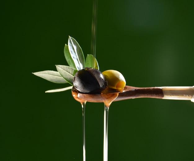 Azeite caindo sobre duas azeitonas com folhas de oliveira para dar sabor a uma salada mediterrânica. Foto Premium