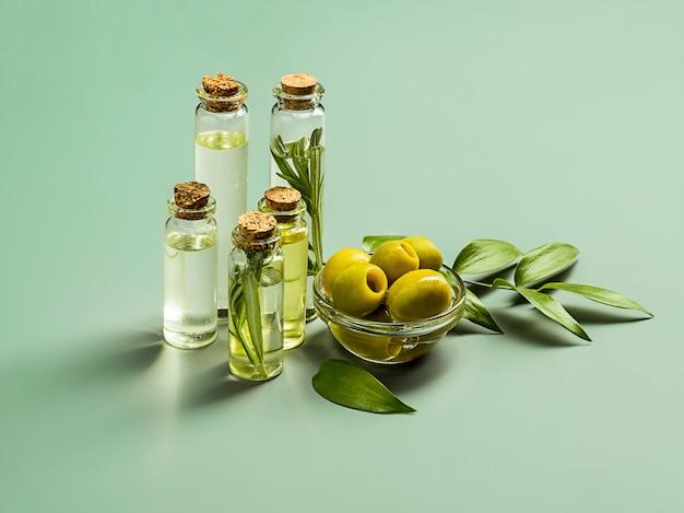 Azeite e ramo de oliveira na mesa de madeira Foto gratuita