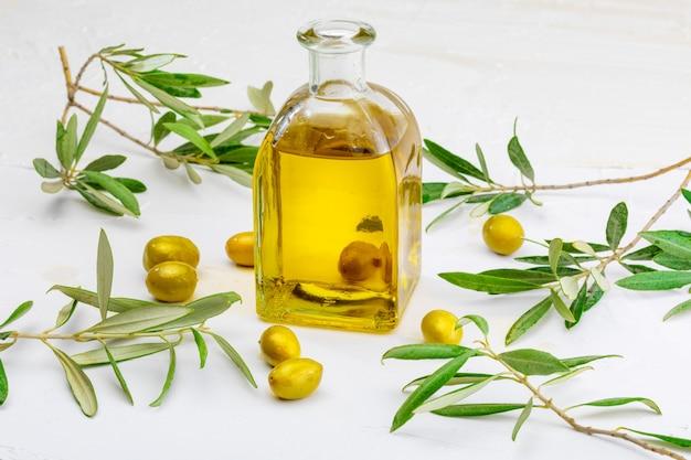 Azeite virgem extra em frasco de vidro. primeiro plano. inclui folhas e ramos de oliveira. Foto Premium