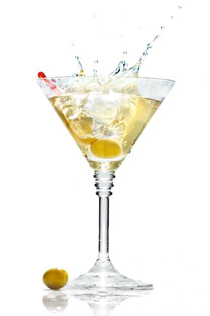 Azeitona espirrando no copo de martini isolado Foto Premium