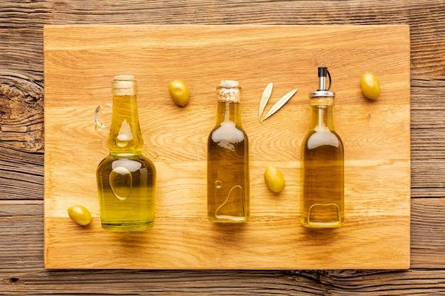 Azeitona garrafas amarelo azeitonas e folhas Foto gratuita