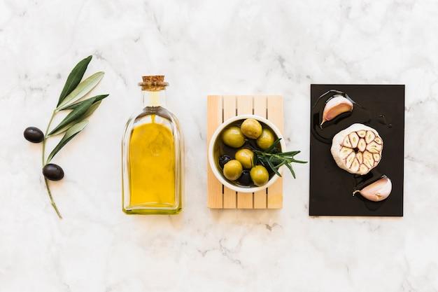 Azeitonas com garrafa e alho e cravo Foto gratuita
