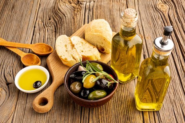 Azeitonas de alto ângulo misturam garrafas de pão e óleo Foto gratuita