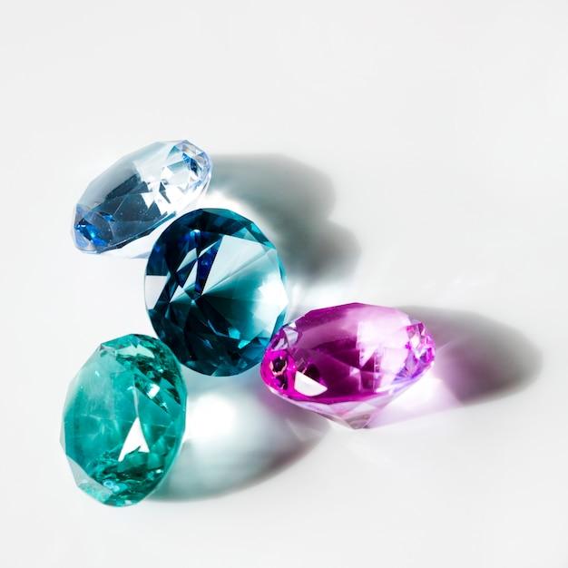 Azul; diamantes brilhantes verdes e rosa com sombra no fundo branco Foto gratuita