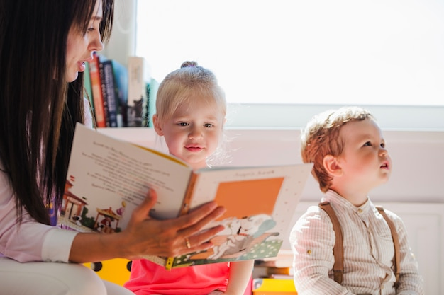 Babá mostrando livro para menina Foto gratuita