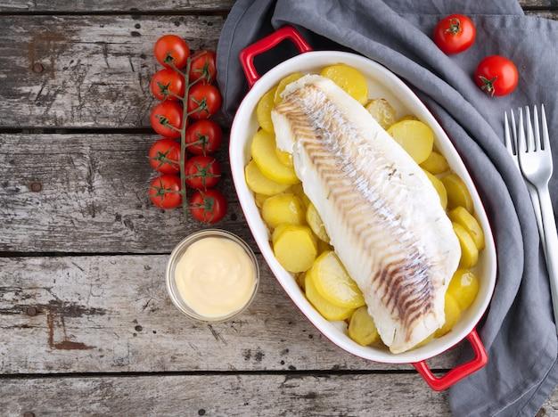 Bacalhau assado no forno com batatas. vista de cima, copie o espaço. Foto Premium