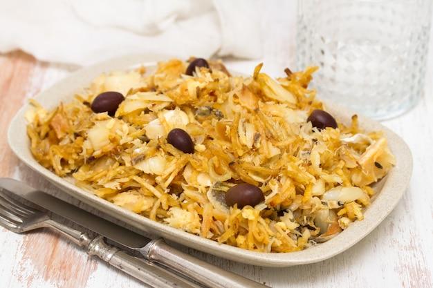 Bacalhau com batatas fritas e azeitonas no prato na superfície branca Foto Premium