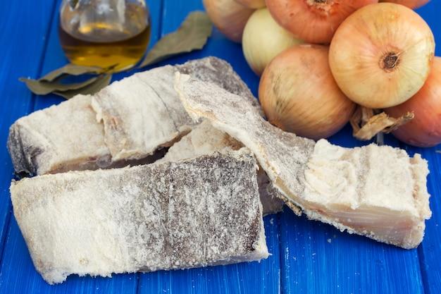 Bacalhau seco salgado com azeite, alho e cebola na superfície de madeira Foto Premium
