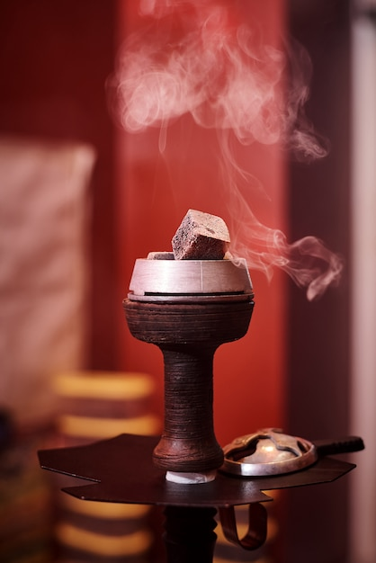 Bacia de cachimbo de água com brasas em uma nuvem de fumaça. Foto Premium