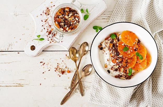 Bacia de granola caseiro com iogurte e tangerina na tabela de madeira branca. comida de fitness. vista do topo Foto Premium