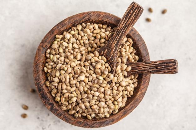 Bacia de madeira de sementes de cânhamo não tratadas. fundo branco, vista de cima. Foto Premium