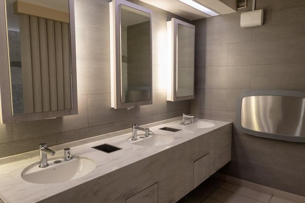 Bacia de mármore de luxo com luz no espelho no banheiro público Foto Premium