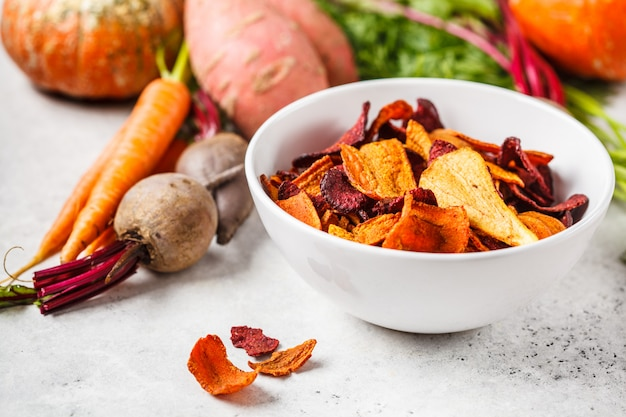 Bacia de microplaquetas vegetais saudáveis das beterrabas, das batatas doces e das cenouras na tabela branca. Foto Premium