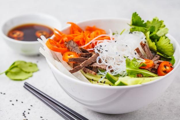 Bacia de salada do cha do bolo. macarrão de arroz vietnamita com carne e salada de legumes pimenta em tigela branca Foto Premium