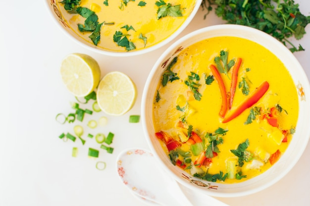 Bacia de sopa fresca do caril com pimenta de sino vermelha, salsa contra o fundo branco. Foto Premium