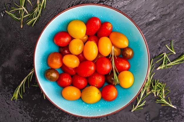 Bacia de tomates de cereja coloridos (vermelho, granada e amarelo), frescos e crus. com gotas de água e alecrim. Foto Premium