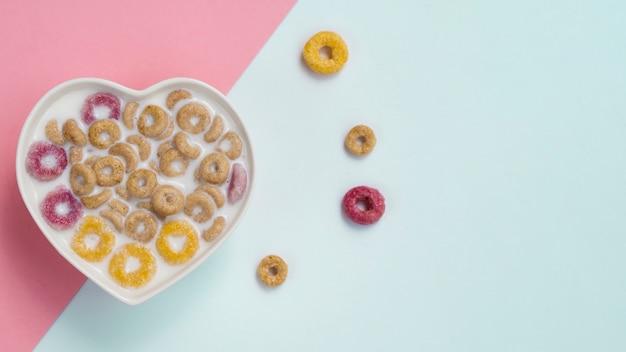 Bacia do coração com cornflakes e laços da fruta Foto gratuita