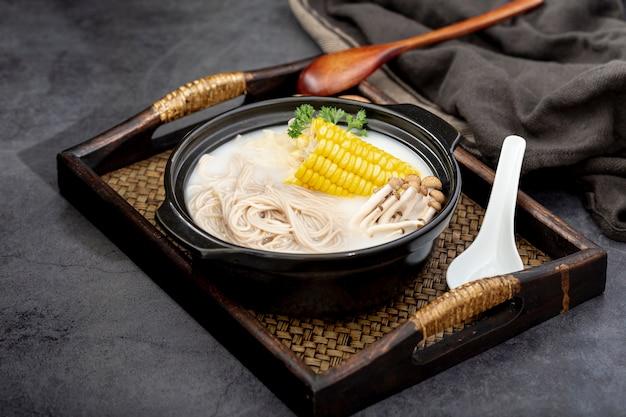 Bacia preta com macarrão e cogumelos com milho em uma mesa de madeira Foto gratuita