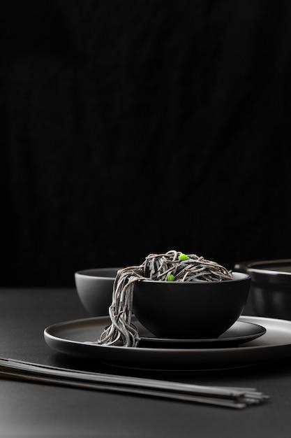 Bacia preta com macarrão em um prato escuro Foto gratuita