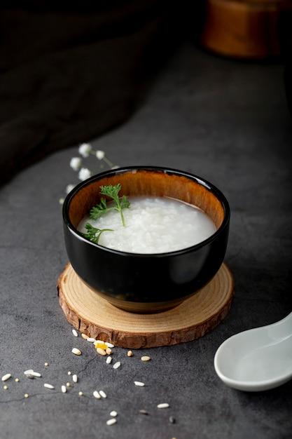 Bacia preta com sopa de arroz em um suporte de madeira Foto gratuita