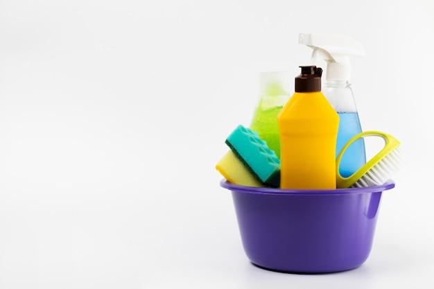 Bacia roxa com diferentes itens de limpeza Foto gratuita