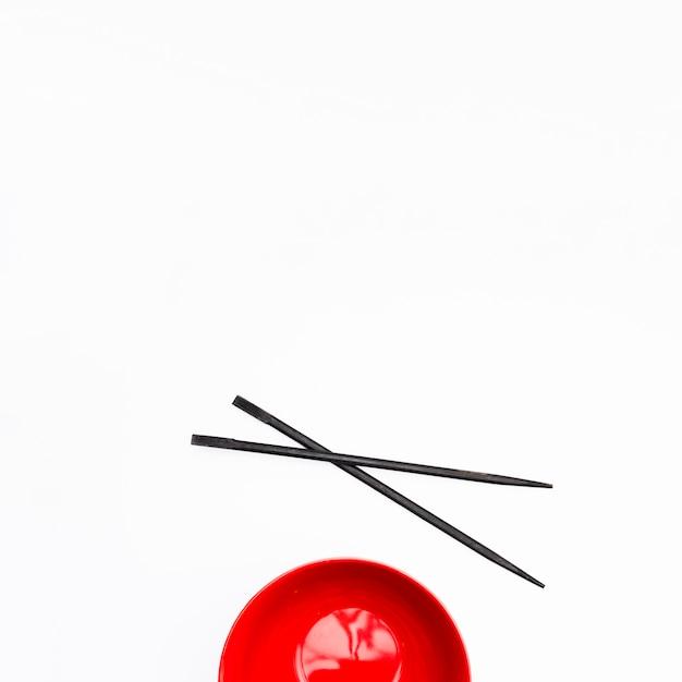 Bacia vermelha vazia e pauzinho isolado no fundo branco Foto gratuita