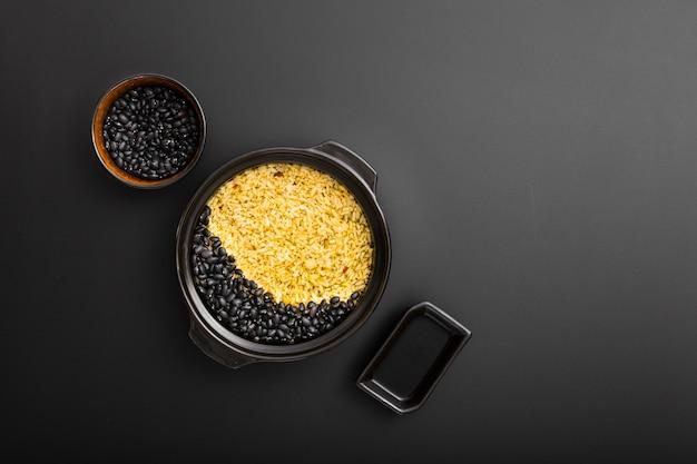 Bacias escuras com arroz e feijão em um fundo escuro Foto gratuita